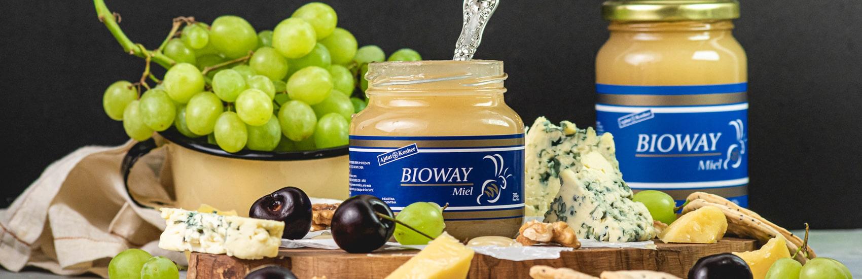 Dos frascos de miel Bioway entre frutas, quesos y galletas.